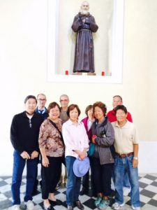 Inside the abbey, the group posed beneath a statue of St. Caprasio. Front row, from left: Wayne Matsunaga, Jan Sakoda, Judy Fukuda, and Ellie and Alvin Shimogaki. Back row: Walter (driver), abbey docent, Carol Matsunaga and David Fukuda. (Photo by Ed Sakoda)