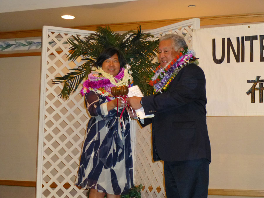 Outgoing president Clyde Matsumoto presents the president's gavel to his successor, Rika Hirata.