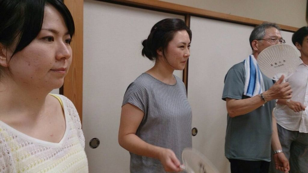 A small obon festival in the neighborhood of Wada in Öshima was moved indoors due to rain. Atsuko Fujimoto, a teacher I met in Öshima, is to my right; her father is to my left.