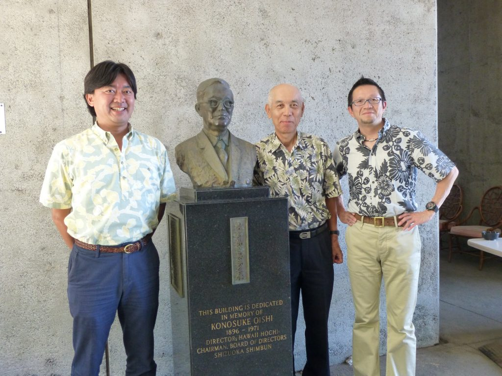 Newly appointed Hawaii Hochi president Taro Yoshida, outgoing president Keiichi Tagata and Shizuoka Shimbun president Go Oishi at the bust of Oishi's grandfather, Konosuke Oishi., who purchased Hawaii Hochi, Ltd. in 1962.
