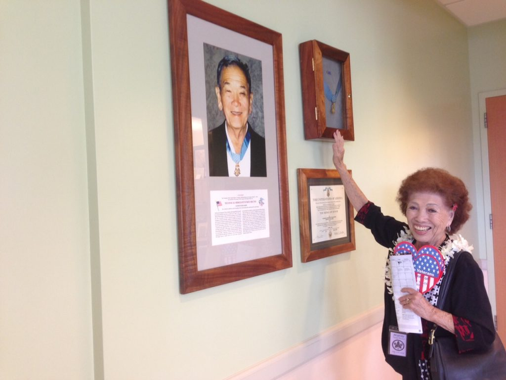 Margie Shinn, Yukio Okutsu's only surviving sister, reaches up to touch the case containing her older brother's Medal of Honor.