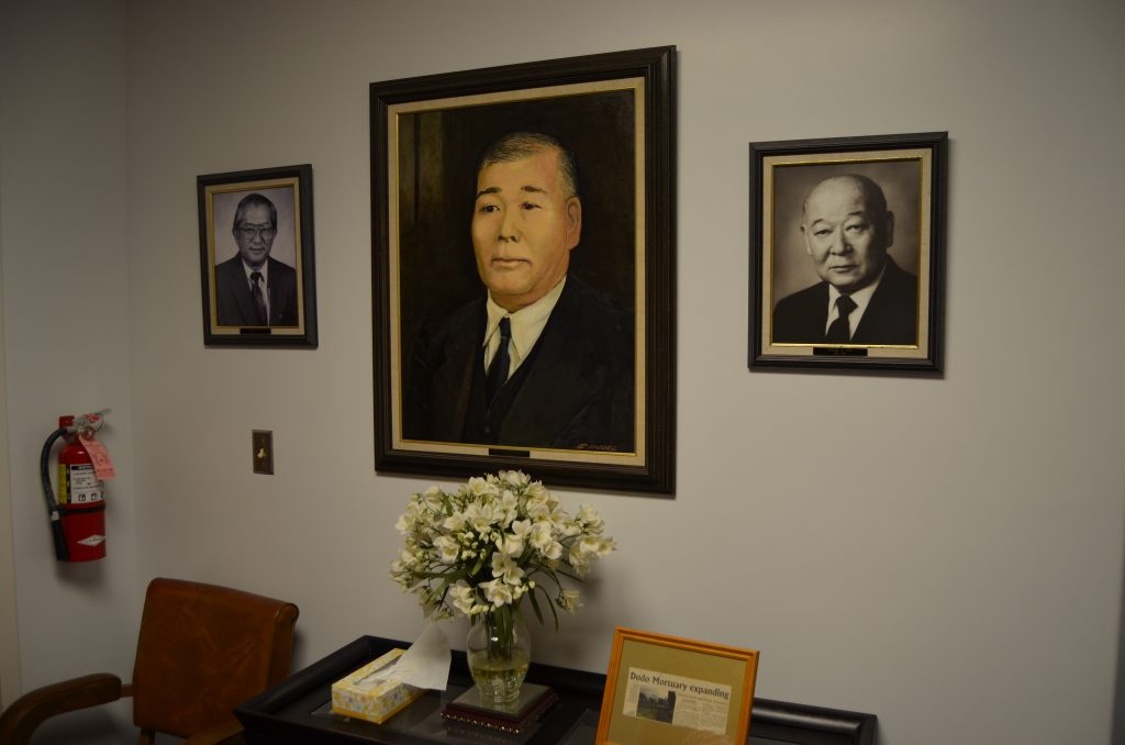 Portrait of founder Mitsugoro Dodo, flanked by photos of son Richard (right) and grandson Clifford (left).