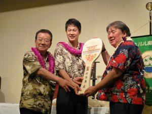 Hiroshima Prefectural Assembly Chairman Naomi Hirata (far left) and Hiroshima Gov. Hidehiko Yuzaki present a ceremonial shamoji to Honolulu Hiroshima Kenjin Kai president Wayne Miyao.