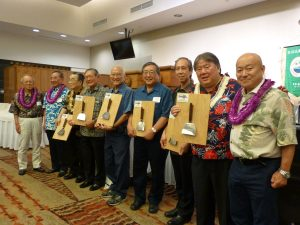 Otafuku Sauce Company chairman Yasufumi Sasaki (far left) and Masao Hayashi, leader of the Hiroshima Prefectural Assembly delegation (second from left), with the outstanding members recognized by the Honolulu Hiroshima Kenjin Kai, all of them holding their trophy okonomiyaki spatulas. From left: Kazukiyo Kuboyama (third from left), Robert Nagao, George Takeuchi, Wayne Toma, Kevin Nakata, Wayne Miyao and Naoyoshi Sasaki, vice president of the Otafuku Sauce Company. (Not pictured: Dan Kinoshita, Benjamin Fukumoto, and Calvin and June Miyamoto).