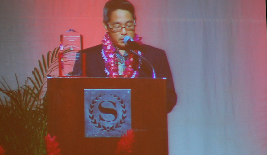 Paul Uyehara, shown on a large screen at the HJCC's general membership meeting, accepts the Generational Award on behalf of Aloha Tofu.
