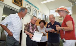 Yoshio Yamamoto, second from left, looks at documents about Tsutomu Ogata, with the help of George (far left) and Jean Ogata (far right), Evelyn Tsuda and then-100th Infantry Battalion Veterans Club president Robert Arakaki.