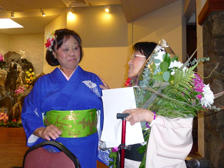 Jo-ann Toma, Onoe Kikunobu-Sensei's first student — and still her student — presents Sensei with a bouquet of flowers and a gift from all of her students.