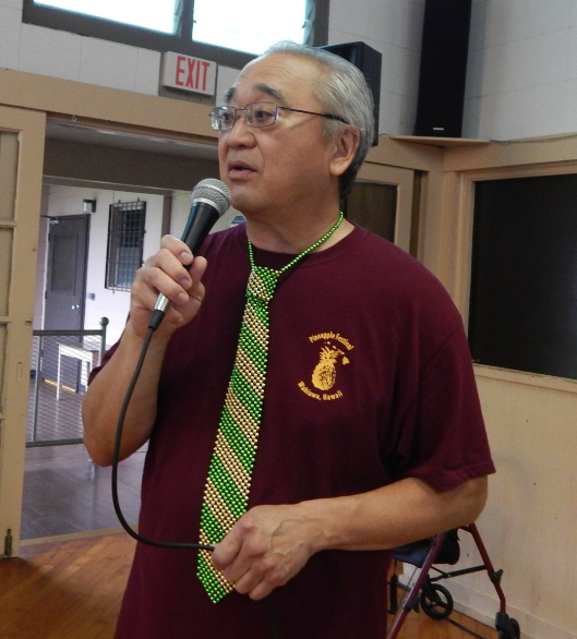 Wahiawa Historical Society president Dr. Jared Kanemaru, sporting a green and gold (Leilehua High School's colors) tie, opens the program and moderates the panel discussion.