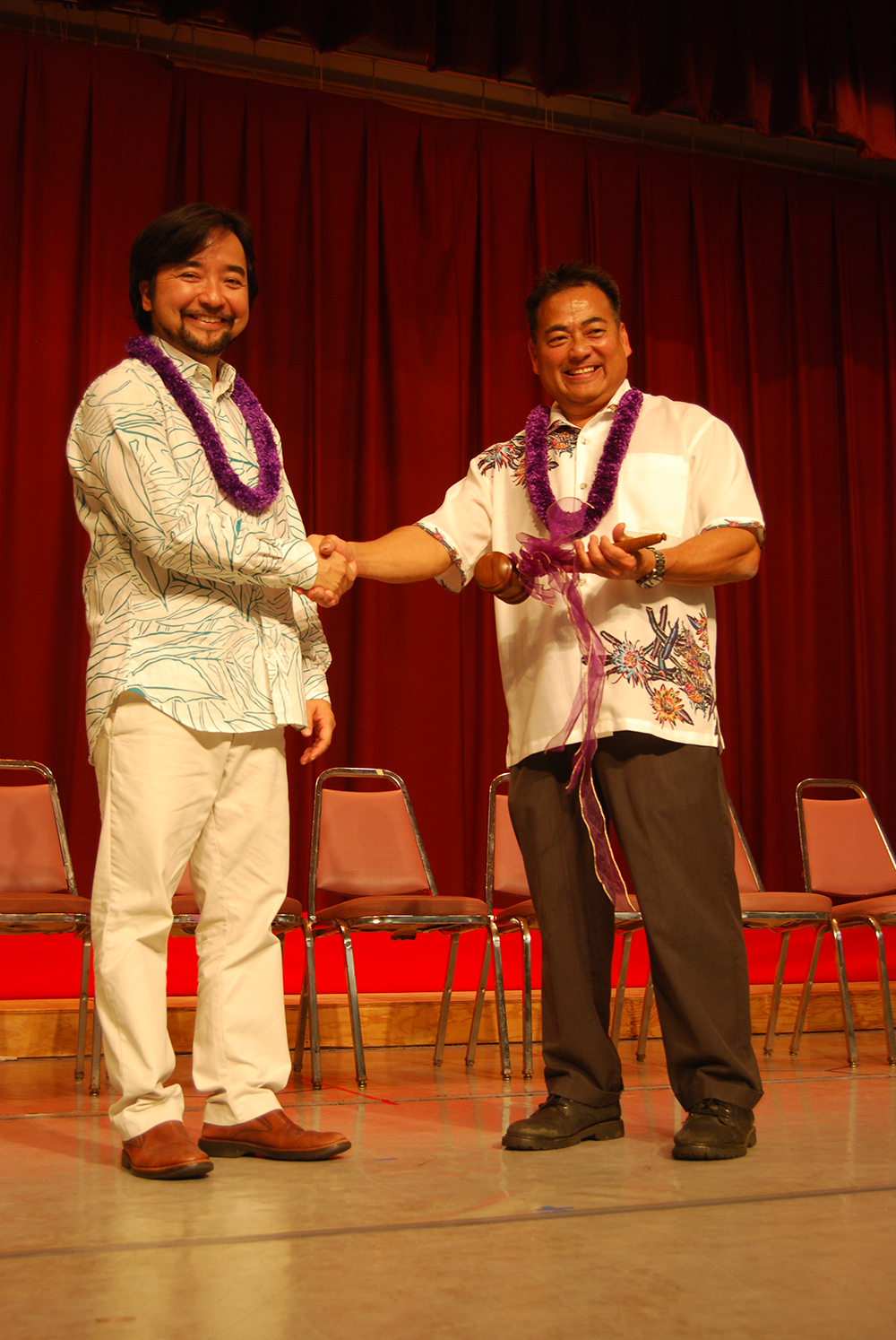 Outgoing president Mark Higa (left) congratulates his successor, Tom Yamamoto, after presenting him the president's gavel.