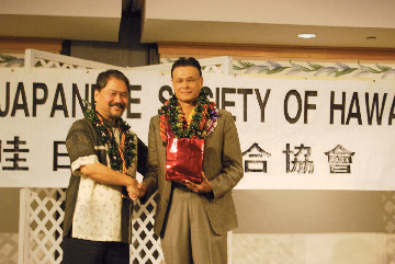 United Japanese Society of Hawaii president Cyrus Tamashiro presents a gift from UJSH to Imperial Decoration recipient Edwin Hawkins Jr. (Photos by Noriyoshi Kanaizumi)
