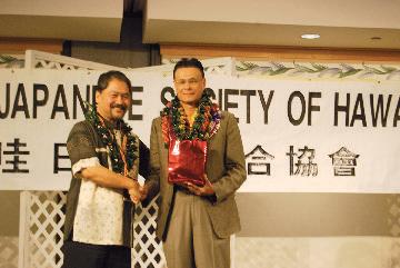 United Japanese Society of Hawaii president Cyrus Tamashiro presents a gift from UJSH to Imperial Decoration recipient Edwin Hawkins Jr. (Photos by Noriyoshi Kanaizumi)