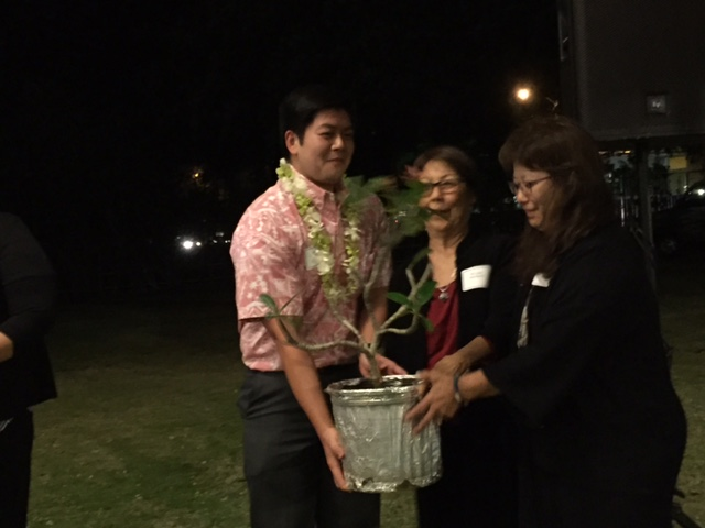 JET Program alum John Anbe and HFKK member June Motokawa present a Singapore plumeria tree to Faye Komagata (far right), wife of Bishop Shugen Komagata of the Soto Mission of Hawaii. The tree, symbolizing Hawai'i's support for the people of the Fukushima and the Tohoku region, was planted on the temple grounds the next day with Bishop Komagata presiding over the ceremony.