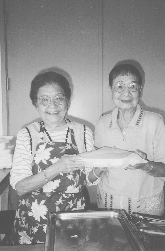 Lanakila members Beatrice Kurogi (left) and Mary Jones volunteer to serve lunches for the Lanakila Meals on Wheels program. (Hawai'i Herald file photo)