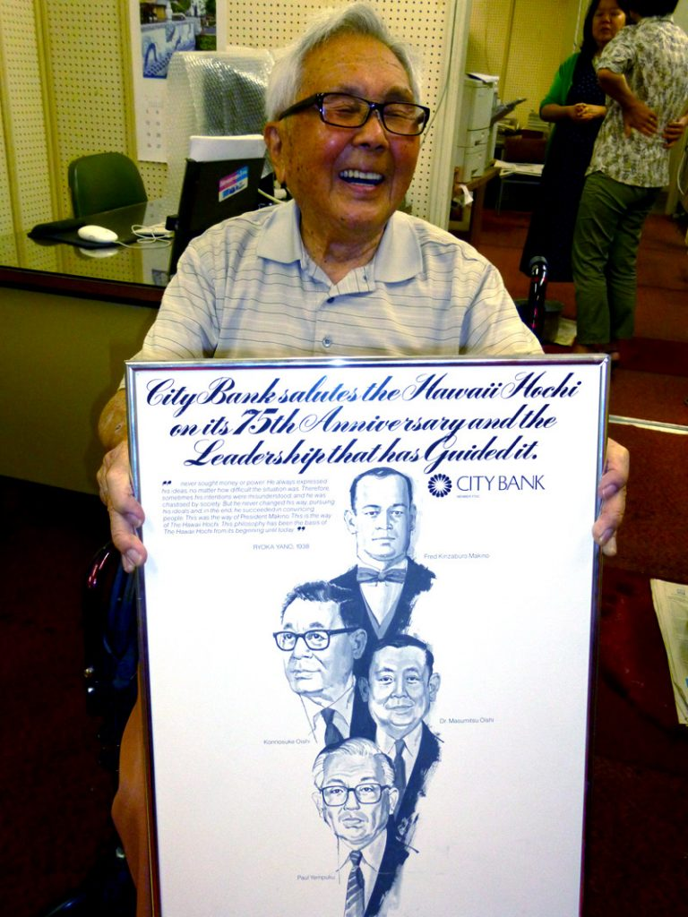 Former Hawaii Hochi president Paul Yempuku displays a framed version of a City Bank ad congratulating (top to bottom) Hawaii Hochi founder Fred Kinzaburo Makino, Shizuoka Shimbun presidents Konosuke Oishi and his son Masumitsu and Hawaii Hochi president Paul Yempuku on the company's 75th anniversary.