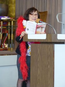 "Photo of Frances Kakugawa reading ""A Feather Boa and a Toothbrush."""