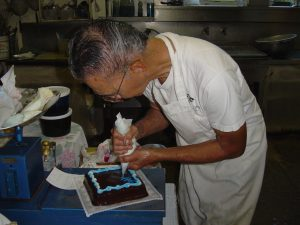Photo of Ikuo Komoda decorating a cake