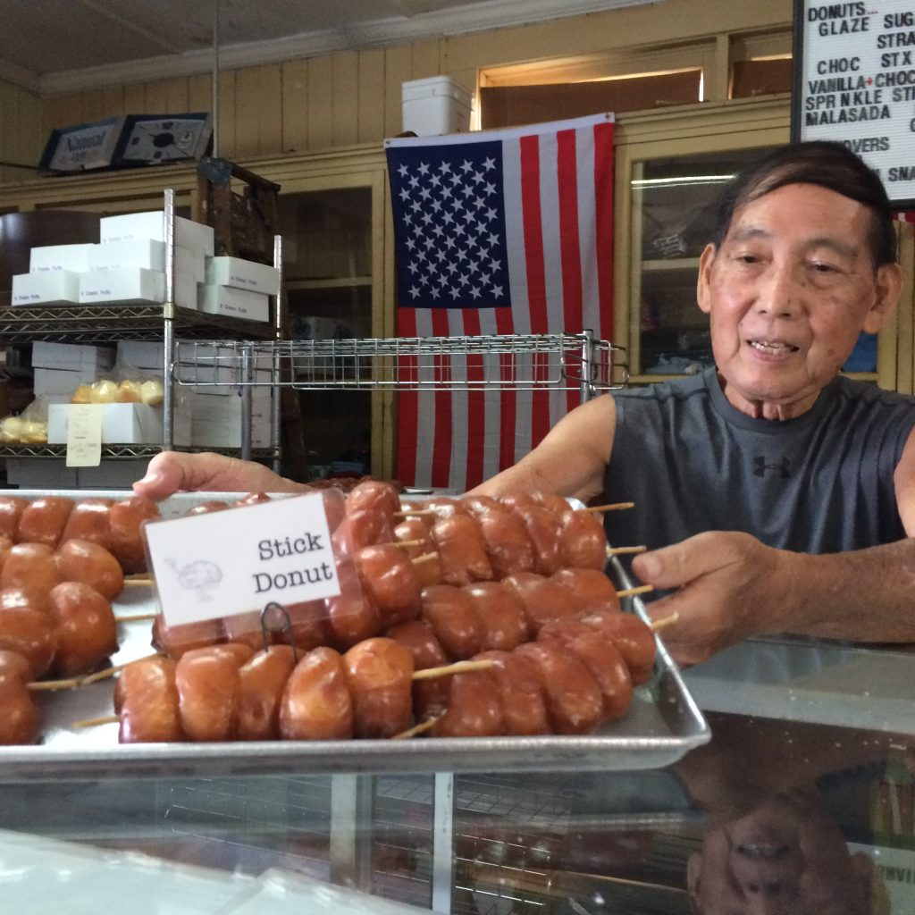 Photo of Calvin Shibuya with a tray of freshly made stick donuts.