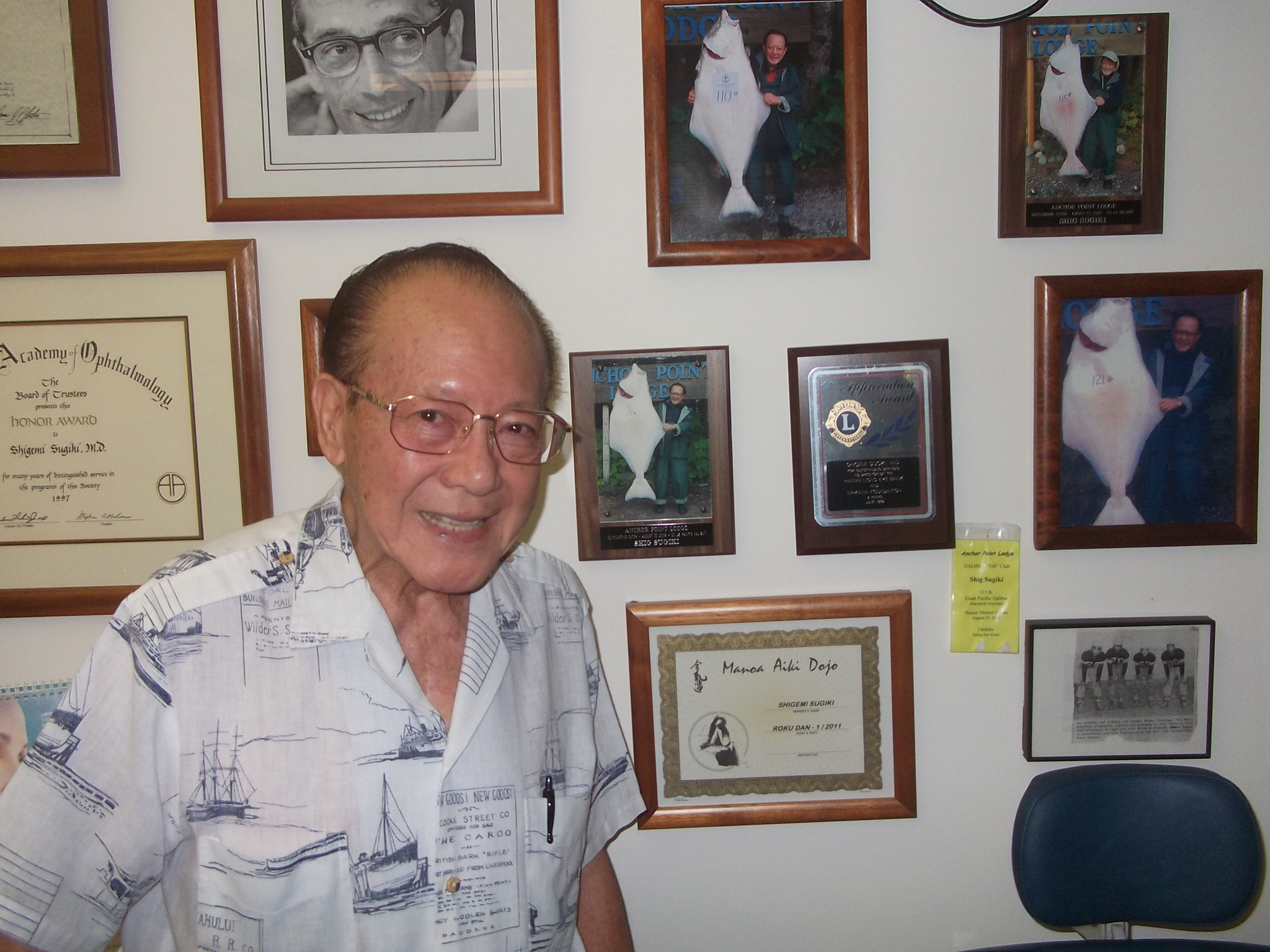 Photo of Dr. Sugiki standing in front of his wall of memories