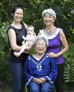 Photo of four generations of Yukimura women: Jennie Yukimura (seated); Maile Walters holding infant daughter Ualani; and JoAnn Yukimura