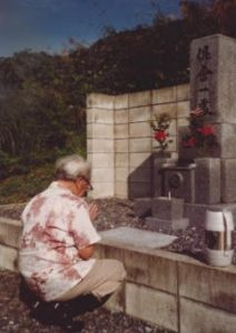 Photo of Kiyoto Saiki (Ken's father) offering a prayer at his father's grave