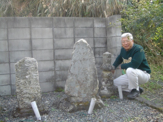 Photo of Ken Saiki next to old family grave markers which have been restored with modern gravestones.
