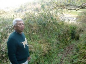 Photo of Ken Saiki visiting the area which his father's home was