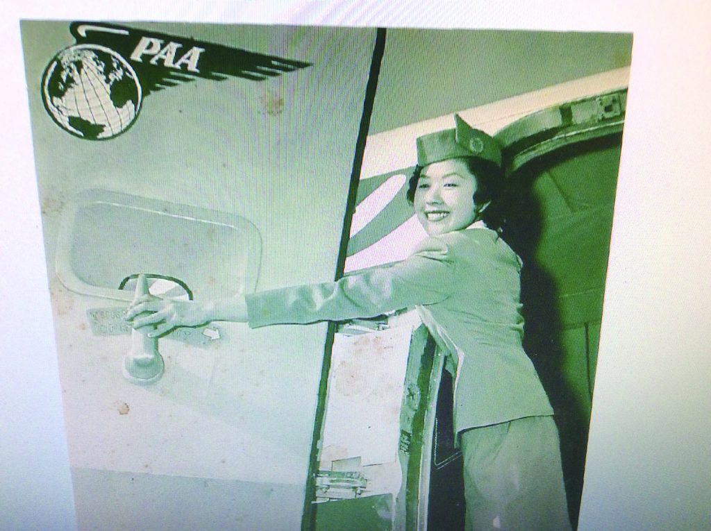 Photo of Marian (Tagawa) Murakami opening the airplane door upon arrival at their destination.