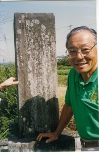 Photo of Sadao Honda in front of a family gravestone