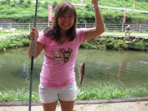 Kellie Iwasaki holds up the yamame (Japanese trout) she caught on a fishing excursion back in 2011