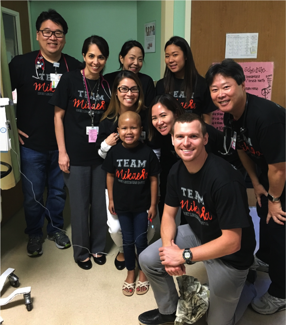 "Team Mikaela! Mikaela with her Kapi'olani medical team — and ""Go Mikaela!"" team — just before being discharged after receiving a haplo-identical bone marrow transplant from her father. Back row, from left: pediatric oncologist Dr. Wade Kyono, pediatric oncology nurse practitioner Dee Ann Omatsu, pediatric bone marrow transplant coordinator Lori Kaneshige and nutritionist Lauren Yasui. Front row, from left: clinical pharmacist Kristi Itagaki, Mikaela, pediatric oncology hospitalist Dr. Kelley Chinen-Okimoto, pediatric intern Dr. Robert Hagbom and pediatric oncologist Dr. Randal Wada."