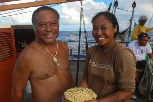 Photo of Kalä Baybayan Tanaka and her dad, Pwo navigator Kälepa Baybayan are all smiles with Tanaka's birthday cake, which was baked at sea and topped with slices of banana. She said turning 34 at sea aboard Höküle'a was a milestone she will never forget.