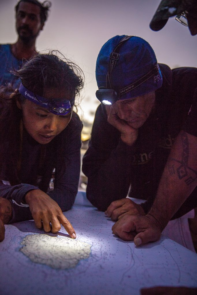 Photo of Tanaka and a fellow crewmember study a map of their island destination. (Photos courtesy Polynesian Voyaging Society)