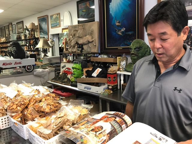 Miyako Sushi owner Michael Kodama looks at a magazine in which he and his collectibles were featured. The collectibles can be seen in the background.