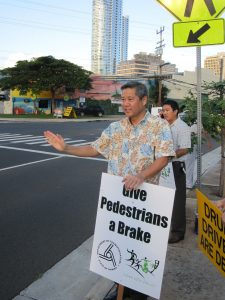 "Cover image of 8/4/17 issue, of Rep. Scott Saiki holding a sign ""Give Pedestrians a Brake"""