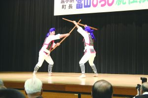 Two guys fighting with sticks on stage at an Okinawan Festival