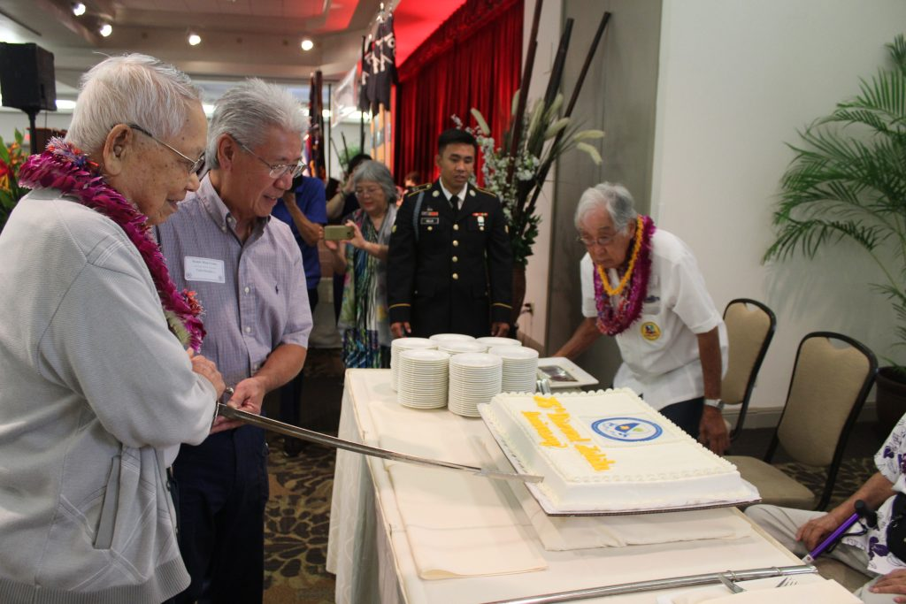 100th Battalion veteran Kazuto Shimizu and 100th Infantry Battalion Veterans president Harry Nakayama cut the 75th anniversary cake with a sword as veteran Moriso Teraoka supervises the cutting.
