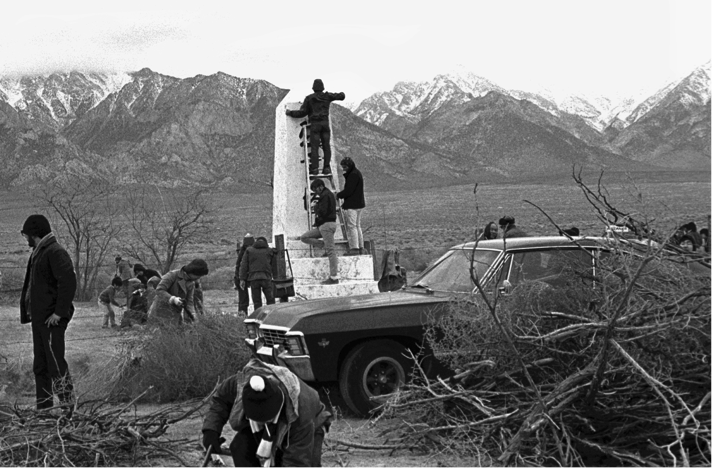 Black and white photo of cleaning the Manzanar Monument on the first pilgrimage in December 1969. (Photo by Robert A. Nakamura)