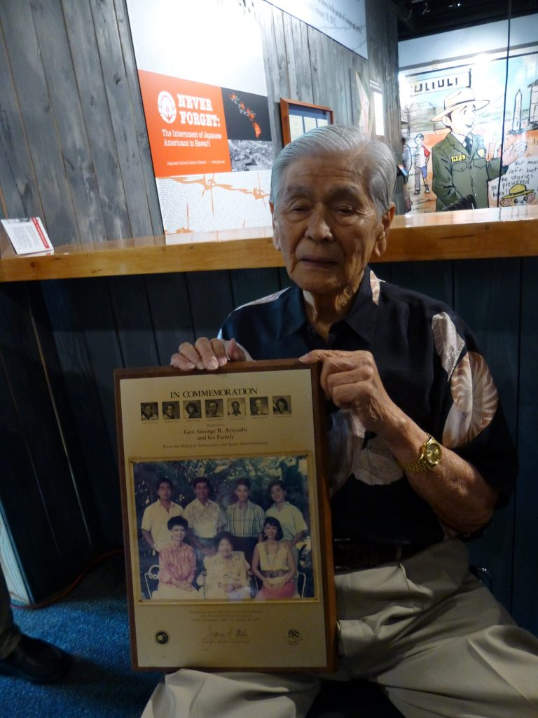 Former Gov. George Ariyoshi holds the photograph of his family that Ellison Onizuka took aboard his ill-fated Challenger mission in 1986. NASA returned to the photo to Ariyoshi, cleaned and framed, after the Challenger tragedy.