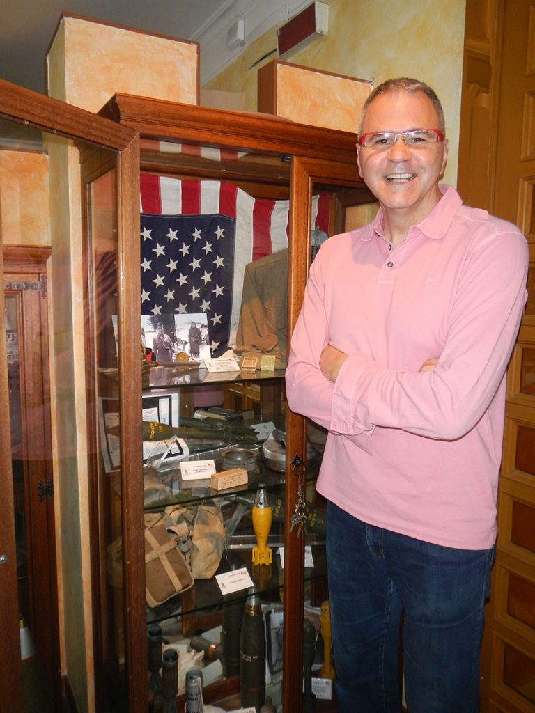 La Pace Hotel owner Pino Valente with his collection of World War II memorabilia, including some items on the 100th/442nd.